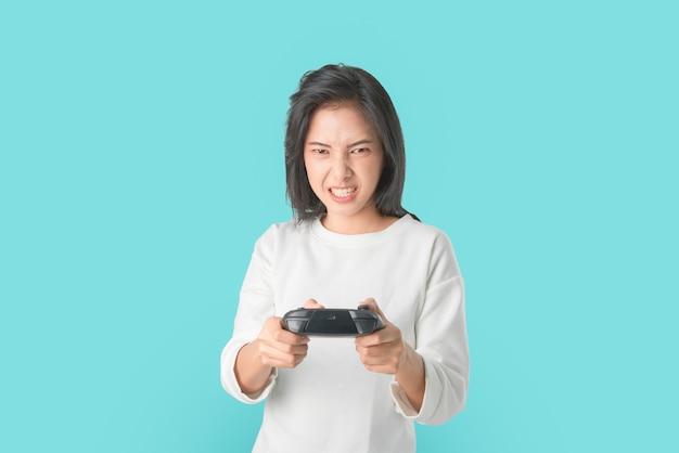 Веселая красивая азиатская женщина в повседневной белой футболке и играющих в видеоигры