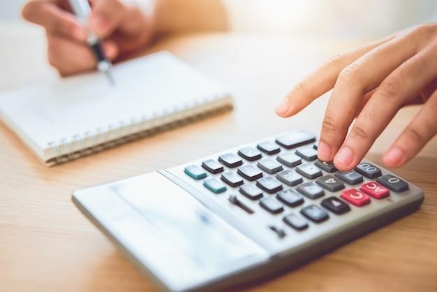 収入支出とホームオフィスでお金を使うための計画を計算する女性持株とプレス電卓。