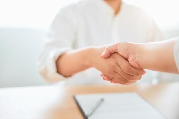 ビジネスを交渉した後成功したパートナーシップハンドシェイクのクローズアップ