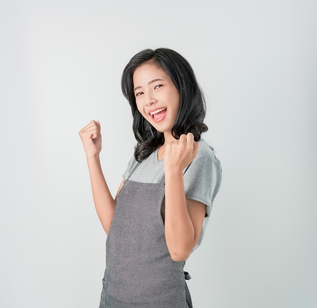 エプロンと立っているアジアの女性の成功に驚くと灰色の背景に楽しみ