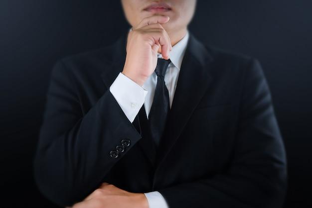 Серьезный бизнесмен в черном костюме руки, касаясь подбородка и глядя.