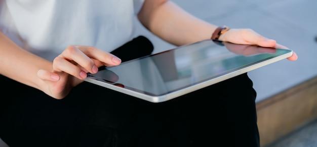 Рука держа таблетку пустой экран на изолированный.