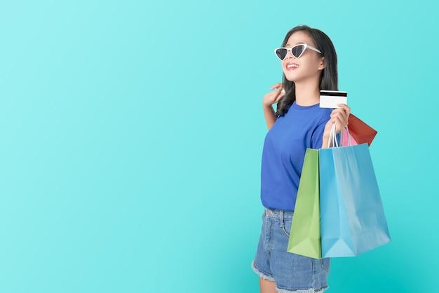 マルチを保持している陽気な美しいアジアの女性は、明るい青の買い物袋とクレジットカードを着色しました。