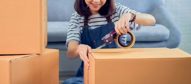 Стартап малого бизнеса, молодая азиатская женщина-владелец, работающая и упаковывающая вещи на коробке покупателю на диване в домашнем офисе, продавец готовит доставку.