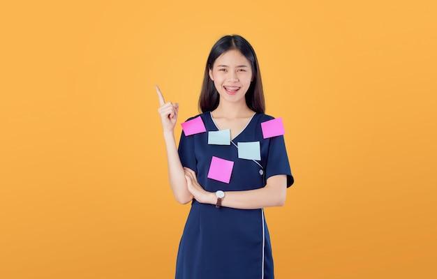Взволнованная молодая азиатская женщина, стоящая, указывая пальцем, чувствуя себя счастливой со скрещенными руками против, размещает заметки на теле, на оранжевом.