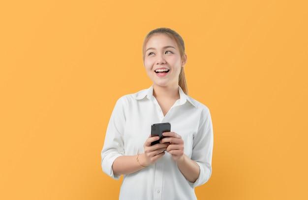 スマートフォンを保持している魅力的な笑顔のアジア女性