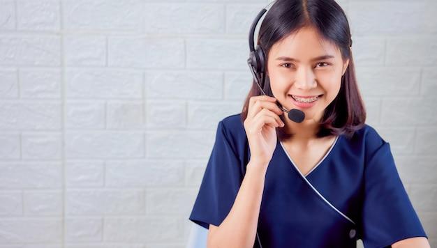 Усмехаясь шлемофон микрофона азиатского консультанта женщины нося оператора телефона работы с клиентом на рабочем месте.