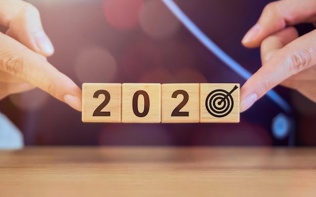 新年と成功の概念、木製のブロックを保持している手の目標