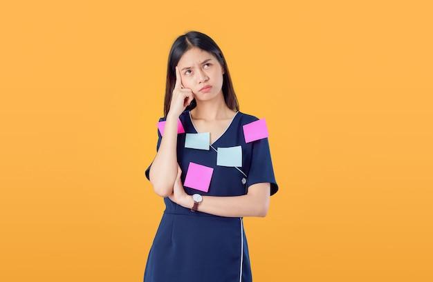 若いアジア女性立っている人差し指と組んだ腕に対して何かを考える、体にメモを投稿
