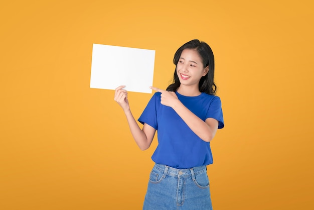 Молодая азиатская женщина держа пустой плакат с усмехаясь лицом и смотреть