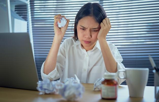 ハードワークとストレスのために強い頭痛や片頭痛に苦しんでいるアジアのビジネス女性。