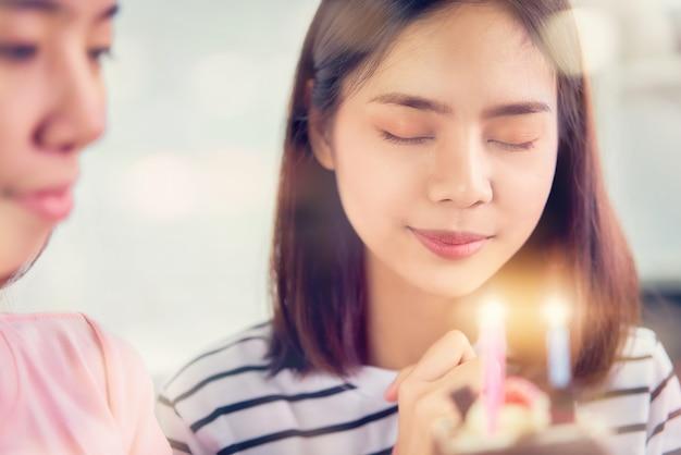 お祝いパーティー、友人が誕生日ケーキを見ている女性。