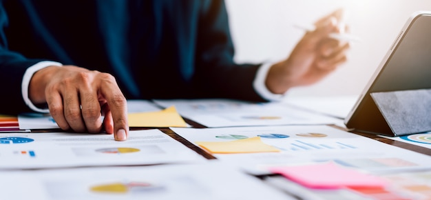 デジタルマーケティング、オフィスデスクの背景にデジタルタブレットとドキュメントを使用するビジネスマン。