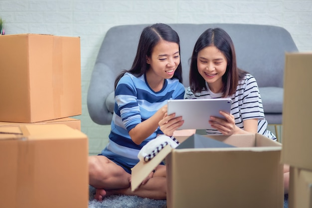 Два азиатских хозяина проверяют заказ клиента у планшета, продавец готовит коробку доставки. концепция запуска малого бизнеса.