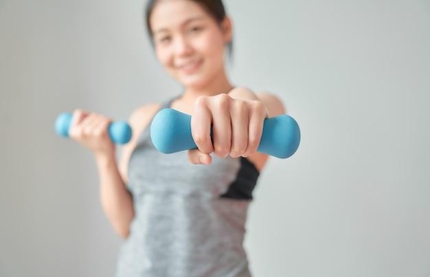 リビングルームで青いダンベルで筋肉をポンピングスポーツウェアを着てスマイリーアジアの女性。健康的なライフスタイルのコンセプト。