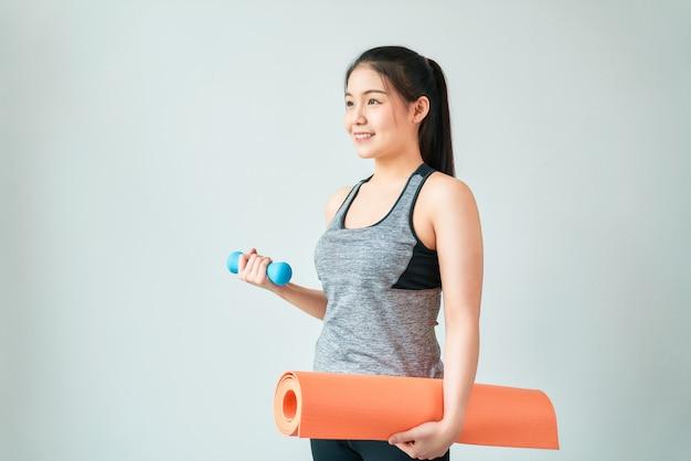 スマイリーアジアの女性は、リビングルームで青いダンベルとオレンジ色のマットを保持しているスポーツウェアを着ています。健康的なライフスタイルのコンセプト。