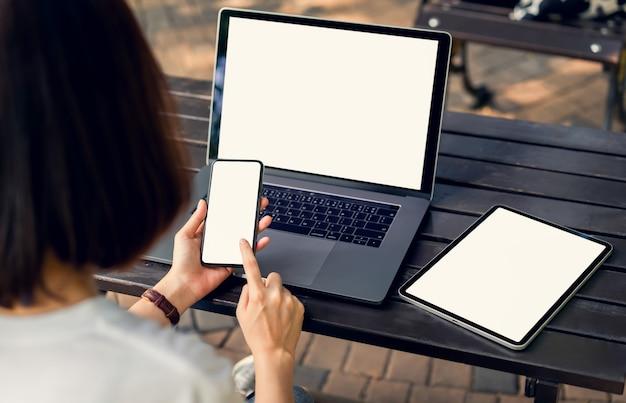 あなたの製品を促進するためにモックアップテーブルの上のラップトップで空白のスマートフォンとタブレットの画面を保持している女性。
