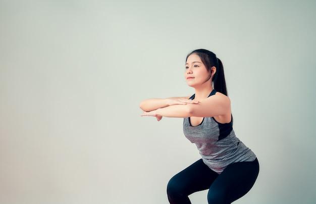 スマイリーアジア女性のスポーツウェアを着て、リビングルームでヨガを練習します。健康的なライフスタイルのコンセプト。