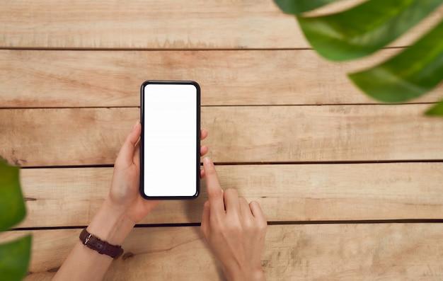 女性の手がスマートフォンを押し、木製のテーブルに空白の画面を押すと、あなたの広告を取る。通信コンセプトの技術。