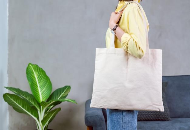 Женщина в вскользь желтой стойке футболки и держать ткань холста сумки для логотипа.