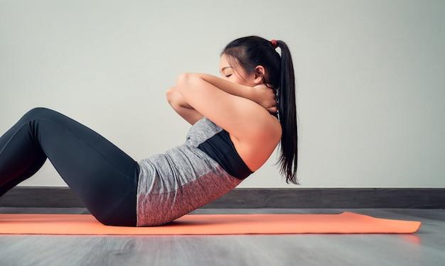 リビングルームでオレンジ色のマットの上に腹筋を行うスポーツウェアを着ているアジアの女性。健康的なライフスタイルのコンセプト。