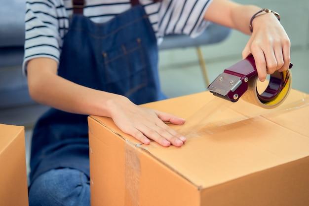 Концепция малого бизнеса запуска, молодой азиатский владелец женщины работая и пакуя на коробке к клиенту на софе в домашнем офисе, продавец подготавливает поставку.