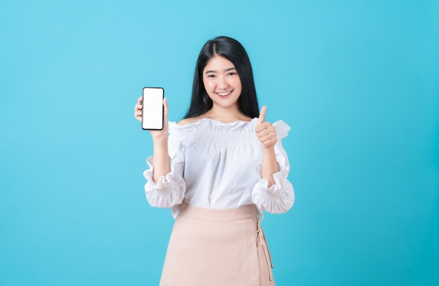 記号のようなショーでスマートフォンを保持している陽気な美しいアジアの女性