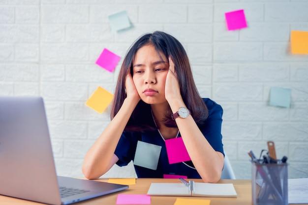 ハードワークと長時間コンピューターを使用することで頭痛を感じるアジアのビジネス女性は、デスクの事務室で体にメモを投稿します。