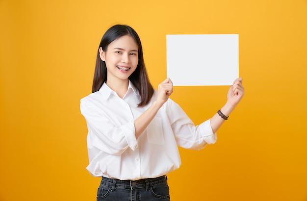 Молодая азиатская женщина держа чистый лист бумаги с усмехаясь стороной и смотреть