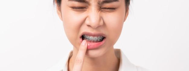Сторона азиатского пальца женщины касается зубной боли возможно из-за плохой заботы.