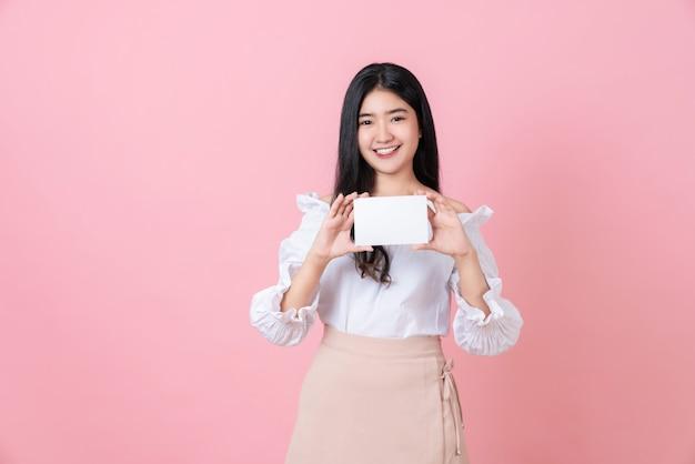 Молодая азиатская женщина держа чистый лист бумаги с усмехаясь стороной и смотря на розовой стене для рекламировать знаки.