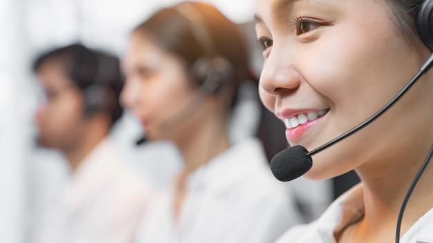 Усмехаясь шлемофон микрофона азиатского консультанта коммерсантки нося оператора телефона работы с клиентом на рабочем месте.