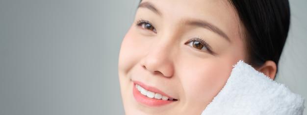 笑顔のアジア女性の美しさのショットは、顔に触れるのに白いタオルを使用します。