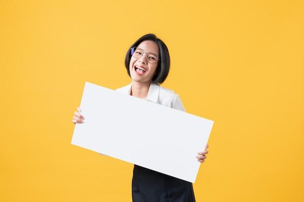 Молодая азиатская женщина держа чистый лист бумаги с усмехаясь стороной и смотря на оранжевой стене для рекламировать знаки.