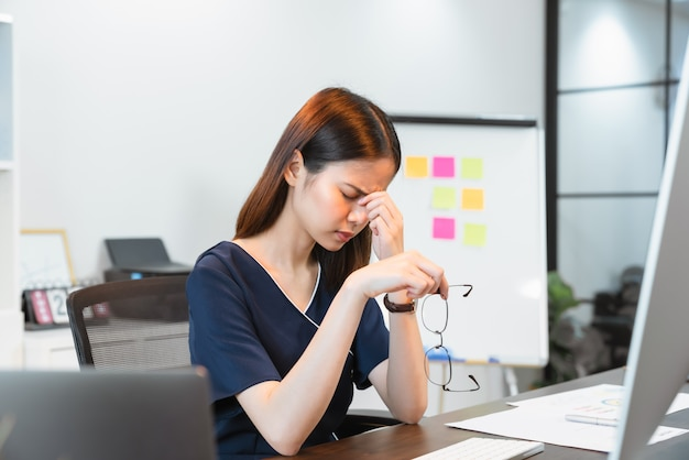 Деловая женщина, касающаяся руками глаз из-за усталости от работающего компьютера в течение длительного времени, может стать причиной офисного синдрома.