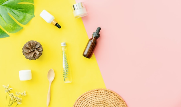Бутылочный крем, макет косметического продукта марки. вид сверху на розовый и желтый.
