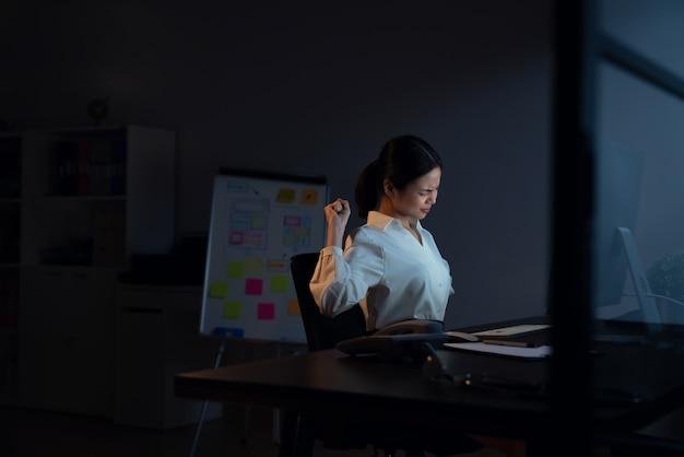 アジアのビジネスウーマンは、コンピューターを使用し、夜に長時間働いているため、首の痛みがあります。