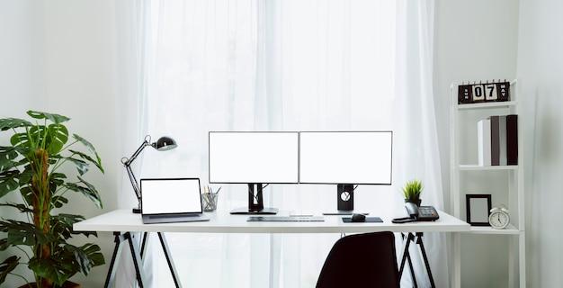 自宅の素敵なデスク、コンピューター、ラップトップ、昼の家のテーブルに空白の画面があり、午後には光が輝いていました。