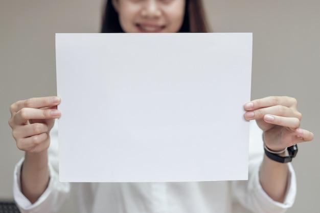 Деловая женщина держит пустую белую карточку. для текстового баннера.
