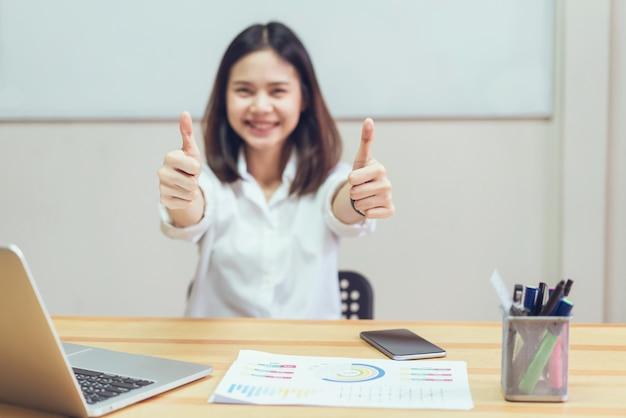 ビジネスの女性はオフィスデスクに座り、ジェスチャーは親指のように見える。