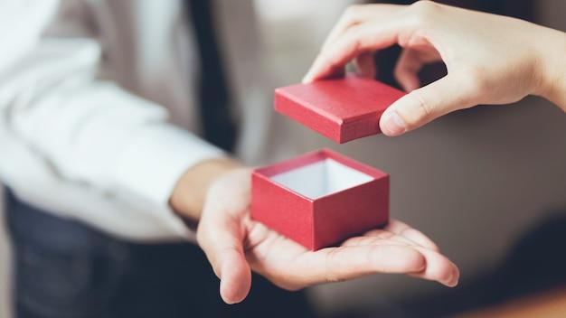 Мужчина держит пустую красную подарочную коробку.