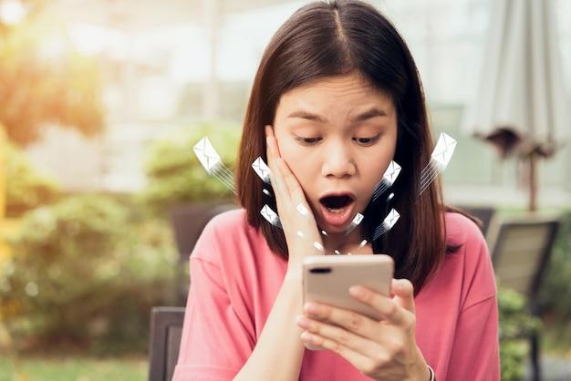 スマートフォンとショーアイコンソーシャルメールを使用している女性