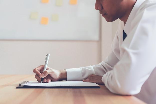 ビジネスマンが書類を書いて、雇用者を再開して仕事の申請を見直す。