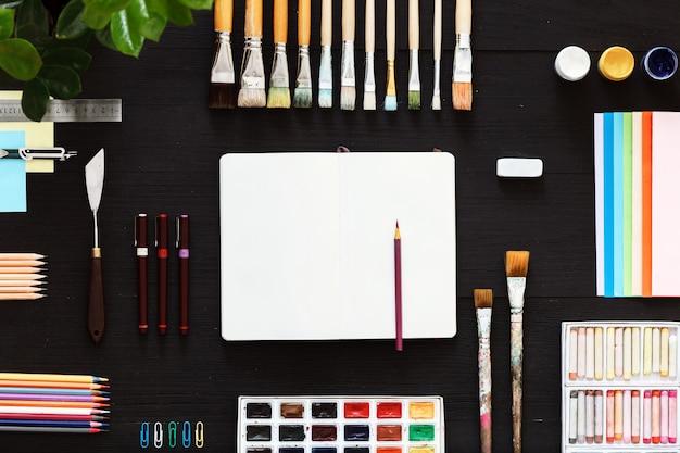 クリエイティブアート作業テーブルコンセプト空白のノートブックペイントブラシとペイントボックス