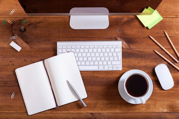 Взгляд сверху тетради клавиатуры компьютера и кофе на коричневом деревянном столе