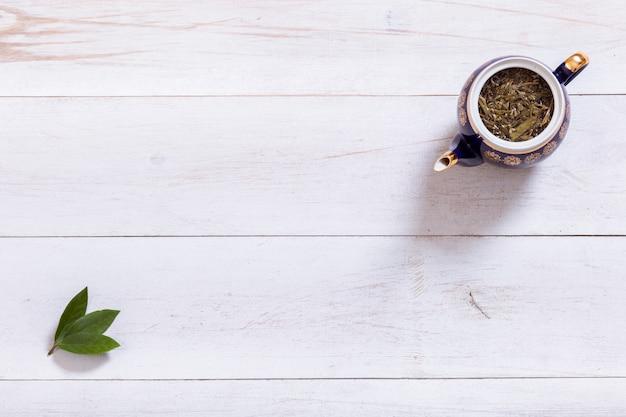 Чайник и чайные листья на белом деревянном столе, вид сверху