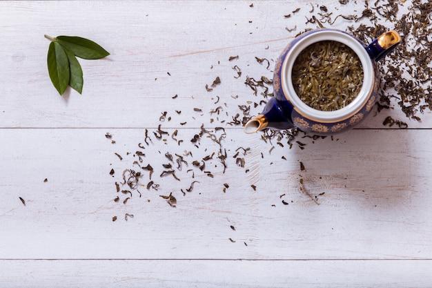 Чайник и сухие чайные листья на белом фоне деревянные, вид сверху, копия пространства