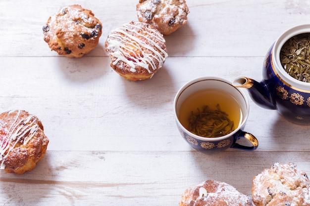 Чашки чая, чайник и кексы на белом деревянном столе, вид сверху крупным планом