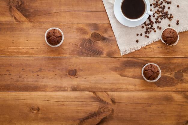 茶色の木製のテーブルの上に散らばってブラックコーヒー、マフィン、コーヒー豆のカップ