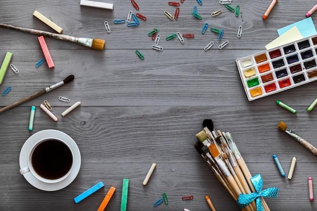 創造的な芸術は灰色の木製のテーブル、描画レッスン、フラットレイアウトの背景を供給します。